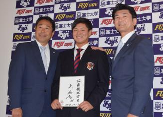 辻発彦監督のサインを手に笑顔を見せる富士大の佐藤龍世(中央)=花巻市・富士大