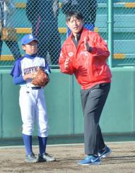 岩隈久志選手(右)からキャッチボールの指導を受ける児童