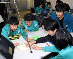 指導役の県立大の学生(右奥)と学校周辺の立体模型図を見ながら、地元の地形について理解を深める寄木小の6年生