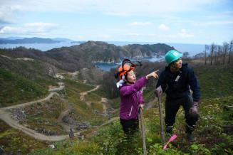 植林体験で参加者に樹木の性質や山林整備の計画を説明する手塚さや香さん(左)。ヘルメットに長靴姿で現場を歩く