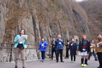 北三陸認定ジオガイド(左)の案内で久慈渓流を見学するツアー参加者