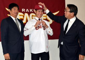 長島哲郎スカウト部長(右)から帽子をかぶせてもらい笑顔を見せる鈴木翔天=盛岡市内のホテル