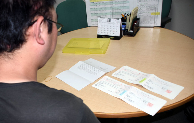 アパートの家賃滞納で届いた督促状を見る男性。ギャンブル依存症に陥り、多額の借金を重ねた