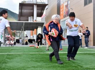 イオンタウン釜石内に開設された人工芝フィールドで、ストリートラグビーを体験する参加者=25日、釜石市港町