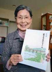 岩手育英会の120年記念誌を手にする戸田洋子さん。奨学生だった日本画家村田林蔵さんが装丁画を寄せた