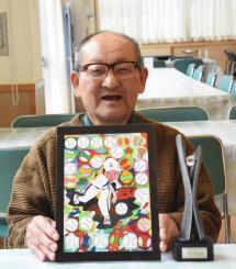 作品のレプリカを手に、受賞を喜ぶ工藤由記雄さん