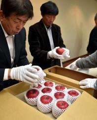 献上するリンゴを丁寧に箱詰めする生産者ら=29日、盛岡市中央通