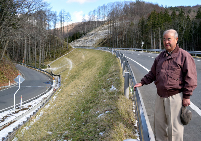 遠野市土淵町の国道340号立丸峠付近の新道から、旧道を見つめる山沢孝士さん