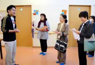 福祉施設を訪れ、施設長(左)の説明を聞く後見人養成講座の受講者。後見人の担い手確保は喫緊の課題だ=盛岡市