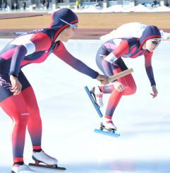 高校女子2000メートルリレー 盛岡工の2走大坪沙紀(左)が3走吉田雪乃にバトンをつなぐ。県新記録をマークした=盛岡市・県営スケート場