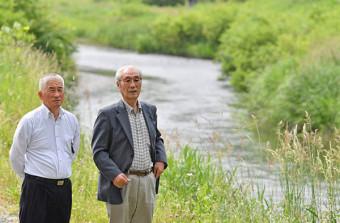小鎚川の川原に立つ平野栄紀組合長(左)と沢山重夫組合長。海、河川それぞれの漁協組合長を務める2人は自然と共生した漁業の在り方を語った=大槌町