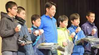 菊池雄星投手(中央)からサインボールなどを手渡され喜ぶ子どもたち