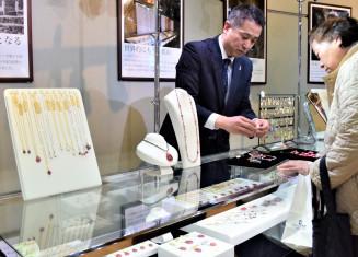赤やピンクの宝石「マリンローズ」をあしらったアクセサリーなどを展示販売する城内義典さん