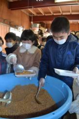 納豆の加工体験で、大豆をすくいあげ小分けする児童ら