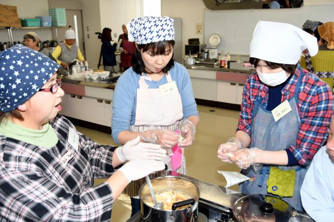 練った小麦粉をひっつかみ、鍋に放り込む参加者