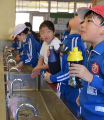 外遊びから戻り、手洗いとうがいをする児童たち