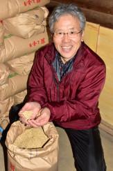 有機JASの認証を受けた飼料用米の品質を確認する織田義信組合長。化粧品などの原料として活用する