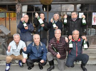 オリジナルの日本酒を完成させて喜ぶ月の輪を愉しむ会のメンバーと西村隆男会長(前列右)、横沢大造会長(同右から2人目)