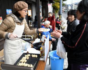 龍泉洞黒豚を使った手作りギョーザを買い物客らに振る舞う針生和美さん(右)