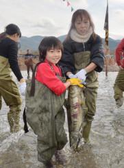津軽石川に放されたサケを捕まえる参加者