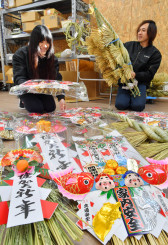 正月飾りやしめ縄の出荷作業に励む鈴木進さん(右)、あさ美さん夫妻=26日、大船渡市末崎町