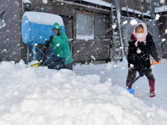 吹雪の中、家の前を除雪する中村敬二さん、シゲさん夫妻=27日、西和賀町沢内