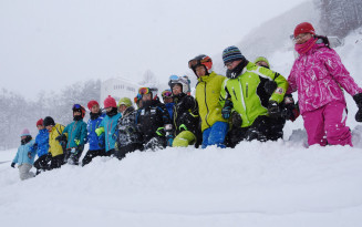 「イチ、ニ」の掛け声とともにスモールヒルジャンプ台のランディングバーンを踏み固める田山スポーツ少年団の子どもたち=29日、八幡平市矢神・田山スキー場
