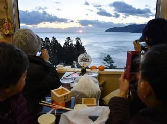 車窓から日の出を望み、写真に収める乗客