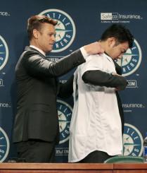 米大リーグ、マリナーズの入団記者会見でユニホームを着る菊池雄星投手。左はディポトGM=3日、米シアトル(共同)