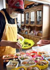 子どもたちの弁当箱に総菜を詰めるNPO法人くちないの高橋晴恵さん