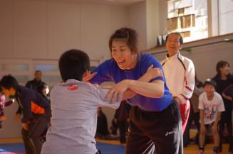 宮古商高のレスリング道場を訪れ、地元の子どもたちと笑顔でスパーリングをする吉田沙保里選手=2012年1月3日、宮古市