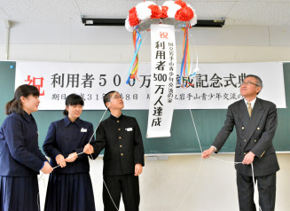 くす玉を割り、利用者500万人の節目を祝う松田栄二所長(右)と下橋中の生徒
