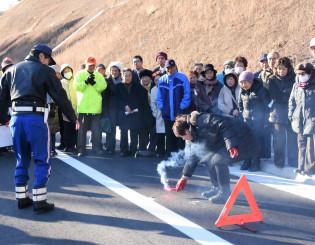 三陸沿岸道路大槌IC付近で発炎筒などを使った緊急時の対処法を学ぶ参加者