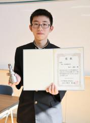 賞状と課題作品を手に金賞での2級合格を喜ぶ福士誠也さん