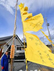 再建した自宅前で、黄色いハンカチを掲げる菅野啓佑さん。地域を元気づけ、着実な復興を見守る=10日、陸前高田市気仙町