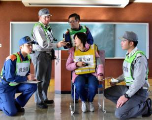 中国語の通訳につないだ携帯電話を傷病者役(中央)に向け、容体を聞き取る参加者