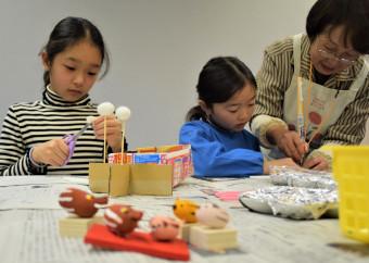 繭を使ってイノシシの人形を作る子どもたち