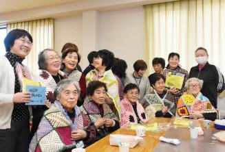 いわて生協から手作りの膝掛けを贈られ笑顔を見せるふれあいサロンの参加者