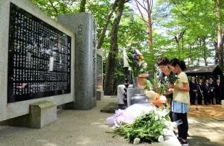 献花拝礼行事で犠牲者の冥福を祈る参列者。会場の「慰霊の森」の施設が大規模改修される=2018年7月30日、雫石町西安庭