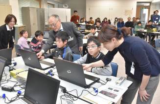 赤松裕子ディレクター(右)らから教わりながらプログラミングを体験する児童