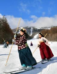 青空の下、はかま姿でゲレンデを滑る子どもたち=12日、雫石町・雫石スキー場