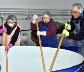 力を込め、櫂入れ作業を体験する参加者たち
