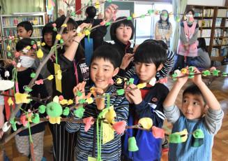 ミズキの枝に色とりどりの団子を飾る子どもたち