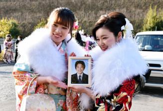 松原啓太さんの遺影と共に同級生と写真を撮る田中彩絵美さん(左)
