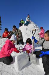 雪のブロックを積み上げ、イグルーを作る子どもたち=14日、葛巻町葛巻・くずまき高原牧場