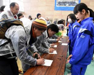 釜石鵜住居復興スタジアムからの避難者の受け付けを行う釜石東中の生徒ら