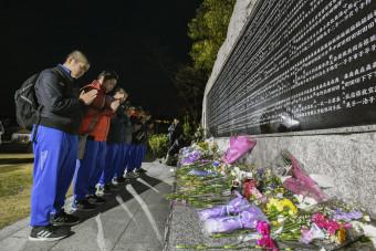 阪神大震災から24年となり、犠牲者の名前を刻んだ石碑に手を合わせる野田村の中学生=17日午前6時25分、兵庫県西宮市の西宮震災記念碑公園