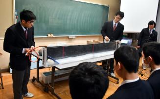 水槽を用いて津波が発生する仕組みを説明する(左から)野沢一生さん、中塚康介さん、本間茜さん