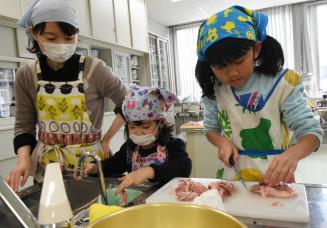 鶏肉を調理する参加者