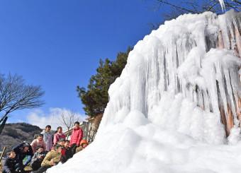 青空の下、3年ぶりに復活した氷柱を笑顔で観賞する子どもたち=19日、盛岡市川目